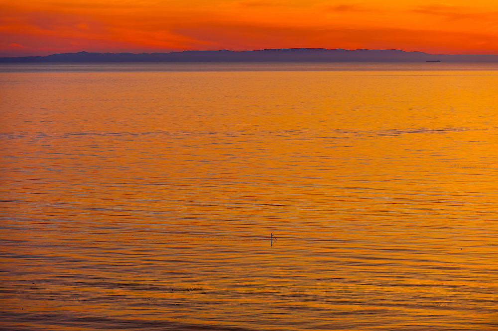 Man paddleboarding in the Pacific Ocean at sunset (Channel Islands in the background), Santa Barbara, California USA.
