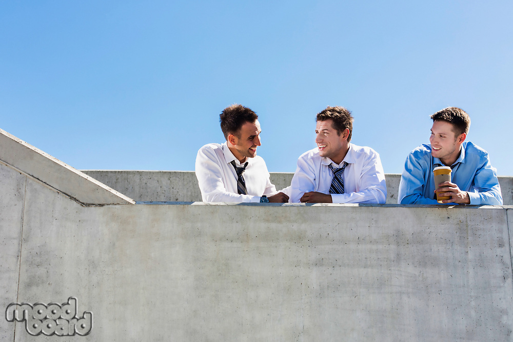 Group of handsome businessmen discussing plans in office rooftop during break