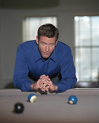 Paul Newman  look-a-like leaning over a pool table