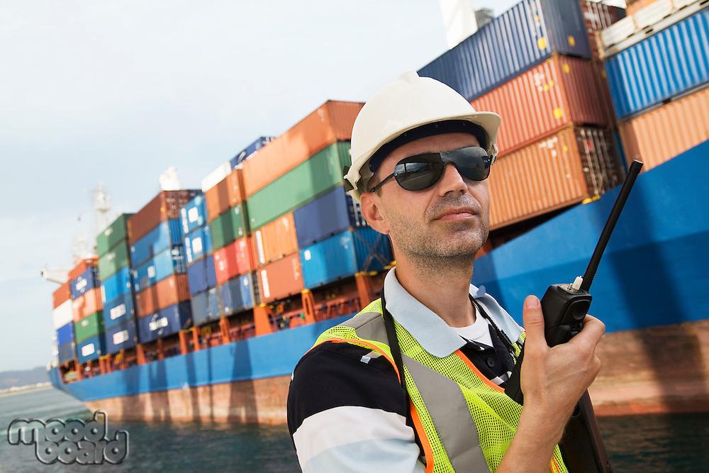 Man wearing hard hat using walkie-talkie at container terminal