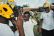 "BIRMINGHAM, AL – SEPTEMBER 10, 2015: Quintarius Monroe (center) enters a huddle during football practice. A type 1 diabetic, Monroe requires frequent blood sugar testing and supervision when self-administering insulin. When care from qualified personnel at his school in Center Point became unavailable, Monroe was forced to transfer several miles away from his locally zoned school to attend Woodlawn High School. The Americans with Disabilities Act requires schools to provide ""reasonable accommodation"" for students with medical conditions, but given that most schools no longer retain school nurses, many schools are failing to provide adequate care for their students.<br />