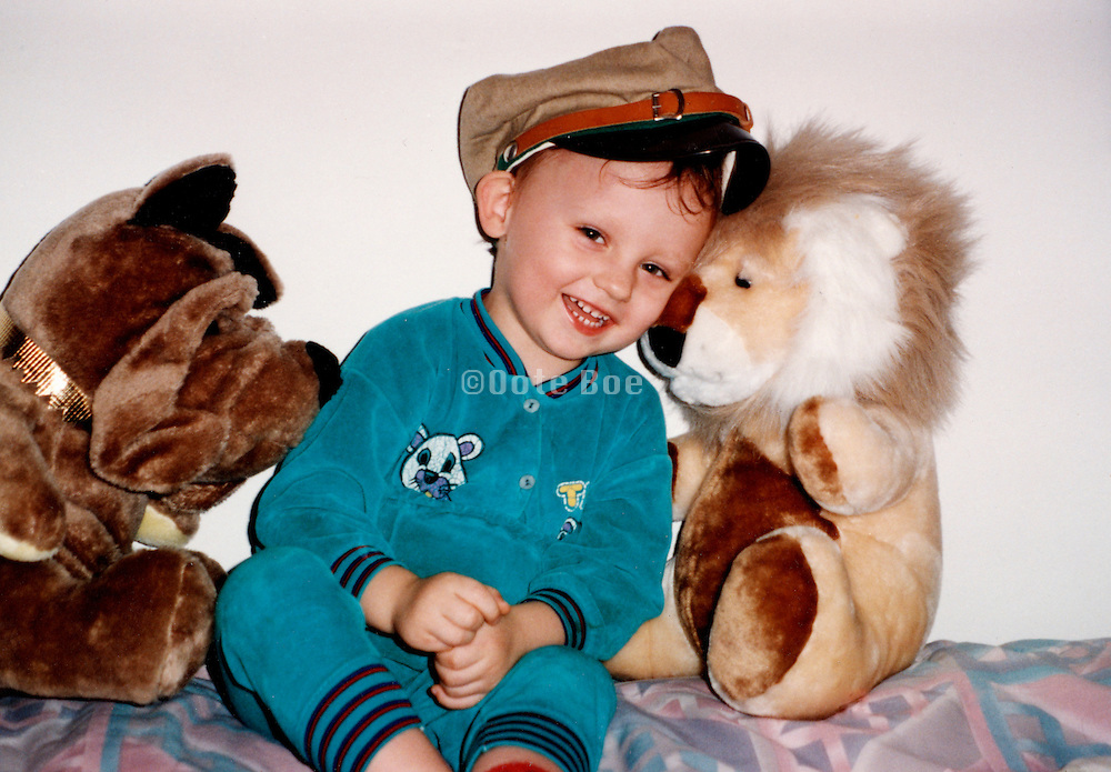 A boy sitting with his stuffed animals smiling to the camera
