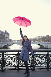 Young woman lifting up a  pink umbrella on a bridge over the Seine river, Paris, France