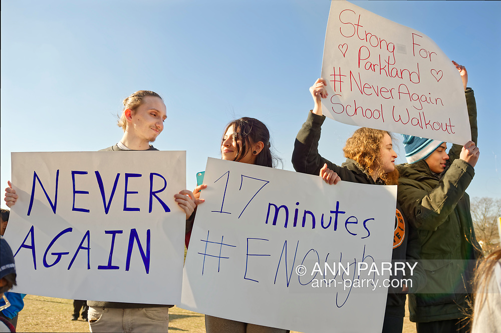 North Bellmore; New York; USA. March 14; 2018. Protesting gun violence, Mepham High School students walk out of class for 17 minutes; starting 10:00 am EST; one minute for each student shot and killed last month in a Parkland, Florida, H.S. Protest signs messages are: NEVER AGAIN, 17 minutes, Strong For Parkland, School Walkout, and have hashtags: #ENOUGH, #NeverAgain. It was part of a nationwide walkout in soildarity with student shooting victims, and a demand for U.S. laws to reduce gun violence.