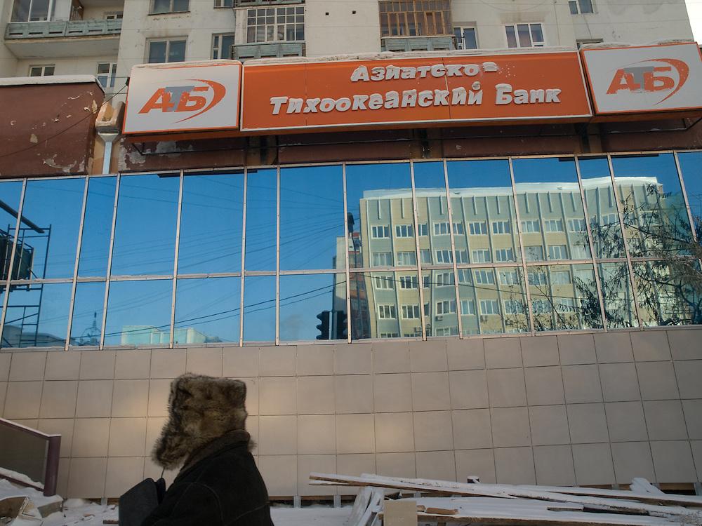 Bank Gebaeude im Zentrum der jakutischen Haupstadt Jakutsk. Jakutsk hat 236.000 Einwohner (2005) und ist Hauptstadt der Teilrepublik Sacha (auch Jakutien genannt) im F&ouml;derationskreis Russisch-Fernost und liegt am Fluss Lena. Jakutsk ist im Winter eine der kaeltesten Gro&szlig;staedte weltweit mit durchschnittlichen Winter Temperaturen von -40.9 Grad Celsius. Die Stadt ist nicht weit entfernt von Oimjakon, dem Kaeltepol der bewohnten Gebiete der Erde.<br /> <br /> Man passing a bank in the city centre of Yakutsk. Yakutsk is a city in the Russian Far East, located about 4 degrees (450 km) below the Arctic Circle. It is the capital of the Sakha (Yakutia) Republic (formerly the Yakut Autonomous Soviet Socialist Republic), Russia and a major port on the Lena River. Yakutsk is one of the coldest cities on earth, with winter temperatures averaging -40.9 degrees Celsius.