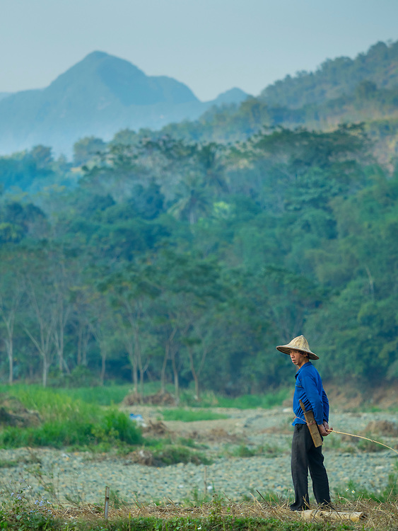 Asia, Vietnam, Pu Luong Nature Reserve. Farmer out standing in his field, wearing conical Non La hat.