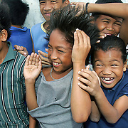 Philippine children react to rotorwash from a US Navy helicopter as it lands emergency aid to a villages destroyed by a landslide.