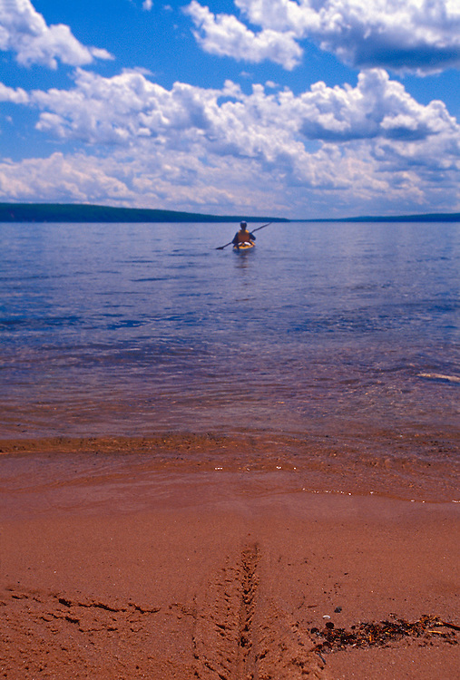 A sea kayaker leaves a beach on Bear Island under puffy clouds while paddling in Apostle Islands National Lakeshore near Bayfield, Wis.