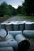 Discarded tar cans sit next to railroad tracks which leads off into the country-side.
