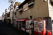 Een vrouw passeert een van de vele drank- en sigarettenautomaten in Osaka