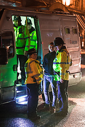 """© Licensed to London News Pictures . 23/12/2017. Manchester, UK. Police handcuff and detain a man on Peter Street . Revellers out in Manchester City Centre overnight during """" Mad Friday """" , named for being one of the busiest nights of the year for the emergency services in the UK . Photo credit: Joel Goodman/LNP"""
