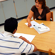Hispanic American Female teaching Assistant testing a Hispanic student in ?CELLA? Comprehensive English Language Learning Assessment ESOL students in Listening and Speaking