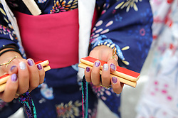 "A young dancer shows some of the specialized rhythm instruments used in the ""bon odori"" dances at the 63rd annual Obon Festival at the Buddhist Temple of Salinas, held Sunday, August 28th."