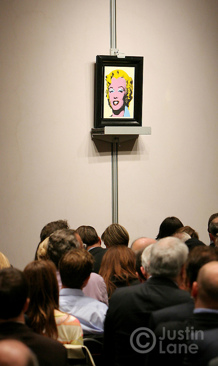 The audience is seen in the foreground as Andy Warhol's 'Lemon Marilyn' (R) is auctioned at Christie's auction house in New York, New York on 16 May 2007. The painting sold for a bid of $28,040,000 (USD) during an auction of post-war and contemporary art.