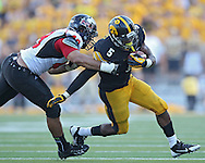 August 31 2013: Iowa Hawkeyes running back Damon Bullock (5) is chased by Northern Illinois Huskies defensive end Jason Meehan (49) during the second half of the NCAA football game between the Northern Illinois Huskies and the Iowa Hawkeyes at Kinnick Stadium in Iowa City, Iowa on August 31, 2013. Northern Illinois defeated Iowa 30-27.