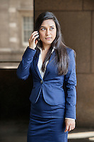 Young Indian businesswoman looking away while using cell phone