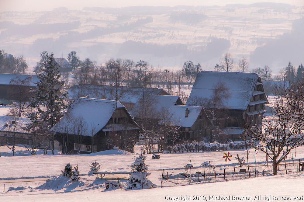 Snowy Swiss farm houses and barns in Hamikon, Switzerland.