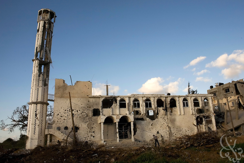 A Palestinian boy plays in front of a destroyed mosque building January 18, 2009 in the Al-Arayis district of Gaza City.Thousands of Palestinian families returned to their neighborhoods today, after 21 days of an Israeli  assault on Gaza that ended with a ceasefire agreement last night.