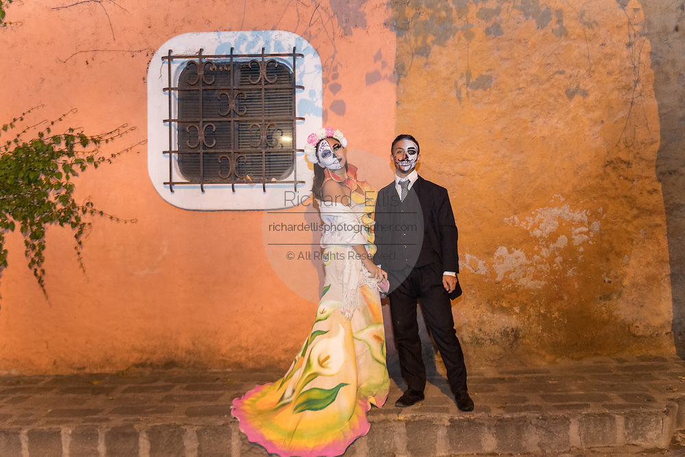 A dressed dressed as La Calavera Catrina and the dapper skeleton pose during the Day of the Dead festival November 1, 2016 in San Miguel de Allende, Guanajuato, Mexico. The week-long celebration is a time when Mexicans welcome the dead back to earth for a visit and celebrate life.
