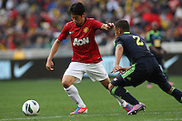Manchester United's Shinji Kagawa against Ajax Cape Town's Nazeer Allie during their International friendly match at Cape Town Stadium