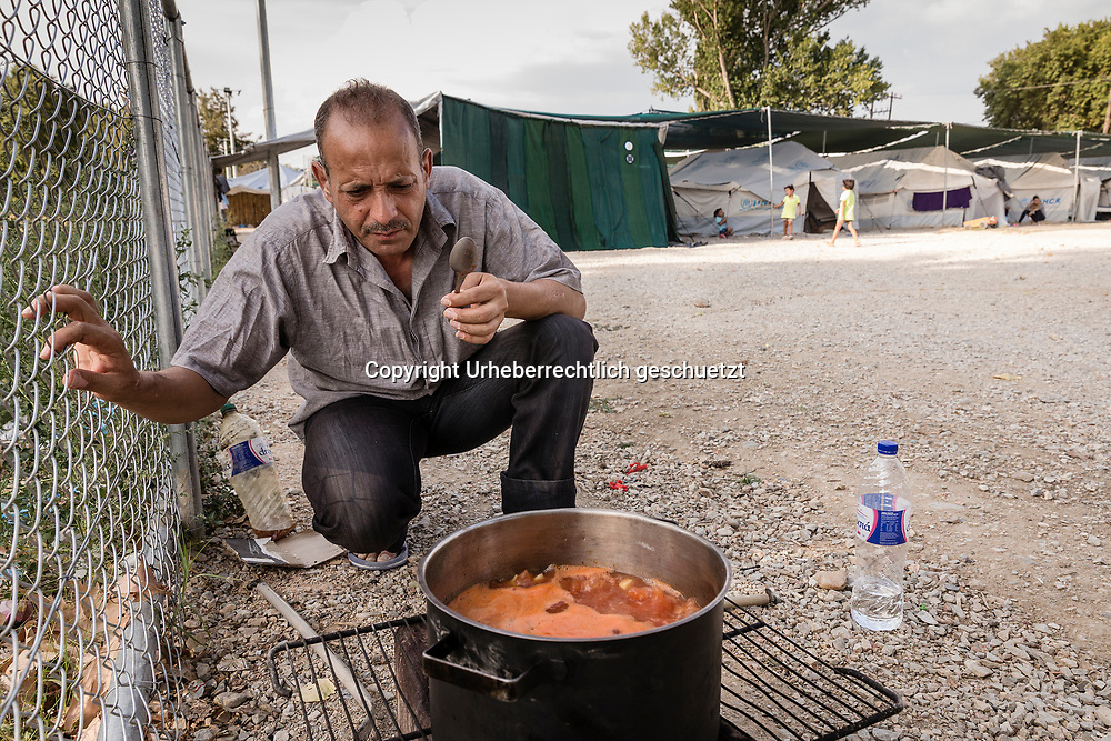 Greece, Lagkadikia, Mohammed ALKAMELL, age 50, Idlip, Syria. Cooking a meal outside the tent, at the fence of the camp. The refugees are not allowed to cook inside the tents or using open fire places like this one. Fireplace made like a small oven, using a big metal box, which is opened on one side above, where the fire heats up the pot.