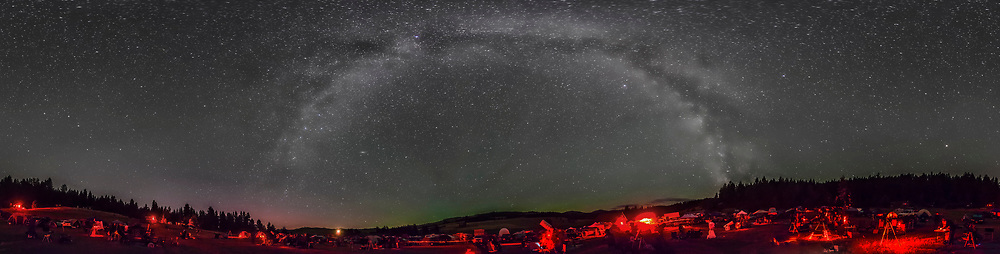 A 360° panorama of the Table Mountain Star Party, July 25, 2014, held at the Eden Valley Guest Ranch in northern Washington state. It shows the Milky Way arching overhead (zenith is at the top), and bands of airglow streaming out of the east at centre. South is to the right of centre where the bright centre of the Galaxy area meets the horizon. The Big Dipper is at the left of the frame. This is an 8-section panorama, with each section shot with a 14mm Rokinon lens in portrait format, at f/2.8 and Canon 5D Mark II at ISO 6400 for 45 seconds each, untracked. Assembled in PTGui using Equirectangular projection. This version of the image has been processed to make the view better resemble what you see with the unaided eye, in a largely monochrome and softer view than the colourful and high-contrast views commonly presented in astrophotos. Even at that there is more fine structure present in the Milky Way than the unaided eye usually sees, though binoculars beging to reveal that smaller detail. I have left some colours in some stars and in the foreground of landscape scenes.