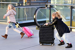 Two excited children run to the check in at London Gatwick airport as the Christmas getaway starts Friday, 20th December 2013. Picture by Stephen Lock / i-Images
