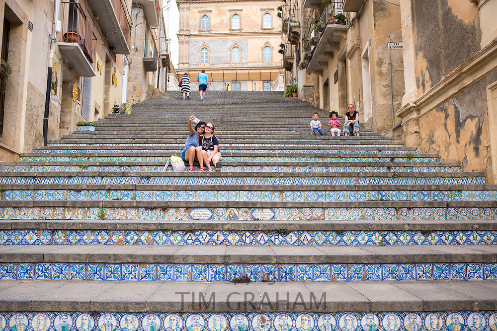 Tourists taking smartphone photograph on famous steps of Scala Santa Maria del Monte stairway at Caltagirone,Sicily