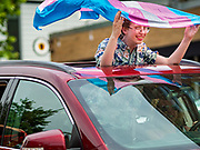 "28 JUNE 2020 - DES MOINES, IOWA: A person with a Pride Flag in the moon roof of a car during the Capitol City Pride Parade in Des Moines. Most of the Pride Month events in Des Moines were cancelled this year because of the COVID-19 pandemic, but members of the Des Moines LGBTQI community, and Capitol City Pride, the organization that coordinates Pride Month events, organized a community ""parade"" of people driving through the East Village of Des Moines displaying gay pride banners and flags. About 75 cars participated in the parade.     PHOTO BY JACK KURTZ"