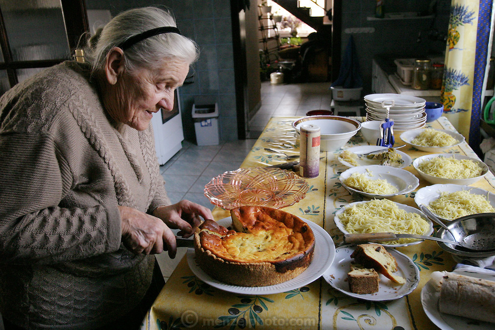 (MODEL RELEASED IMAGE). In her farmhouse kitchen in the village of Adamka, in central Poland, 93-year-old Maria Kwiatkowska (Hubert Sobczynski's friend Borys's grandmother) slices the cheesecake she baked for the traditional family gathering on All Saints Day. After visiting the graves of their relatives in the local cemetery, her children and grandchildren descend on her for a splendid lunch of noodle soup with cabbage and carrots, pork roast stuffed with prunes, pickled pumpkin, a fruit-nut roll, and cheesecake. Hungry Planet: What the World Eats (p. 250).