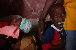 Franty Jean, 3, cries next to his un-named 3 day old brother, just 3 days after their mother, Kele Tintin,  was caught in the middle of gang warfare and killed on her way to work.  Tintin stayed alive long enough to give birth to a son the same day, and died 6 hours later.    The security situation in Cite-Soleil, one of the most dangerous slums in Haiti,  has deteriorated over the past few months with two warring gangs controlling the entire town.  In Project, the side of town controlled by a pro-aristide gang, the market had to move away from the border zone, people take creaky, wooden boats across the harbor instead of crossing the dividing line, and children are threatened with death if they attempt to cross the line on their way to school.