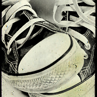 A pair of black baseball boots with white laces