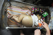 DONGYANG, CHINA - AUGUST 22: (CHINA OUT) <br /> <br /> 15-month-old Girl Has A Big Belly In Dongyang<br /> <br /> Wang Wenjun takes care of his 15-month-old daughter Wang Feng born with congenital biliary atresia on August 22, 2013 in Dongyang, Zhejiang Province of China. A expert at the Children's Hospital of Fudan University told the poor family that the disease is treatable, but the medical expenses are very expensive, needing at least 200,000 yuan (32,600 USD). Wang Wenjun with an atrophied right leg due to poliomyelitis works as a doorman with monthly salary of 1,000 yuan (163 USD), and his wife has mental disability. <br /> ©Exclusivepix