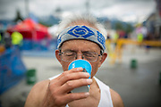 Chad Resari, 2017's oldest racer at 81 years, drinks up at the finish line.