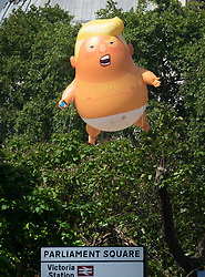 © Licensed to London News Pictures. 13/07/2018. London, UK. A giant inflatable balloon depicting President Trump as a baby in a nappy is flown over Parliament Square. President Trump is on the second day of a four day visit to the UK. Photo credit: Peter Macdiarmid/LNP