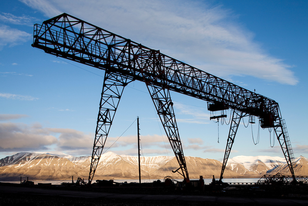 Norway, Svalbard, Pyramiden, Silhouette of loading crane along waterfront at abandoned Russian coal mining settlement on summer evening