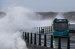 © Licensed to London News Pictures. <br /> 21/03/2015. <br /> <br /> Sandsend, North Yorkshire.<br /> <br /> A bus drives along the coast road as huge waves crash against the sea wall at Sandsend in North Yorkshire. The exceptionally high Spring tides were created by the moon's 18-year cycle.<br /> <br /> Photo credit : Ian Forsyth/LNP