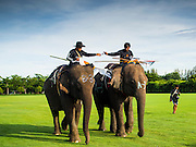 """28 AUGUST 2014 - BANGKOK, THAILAND:   Mahouts ride their elephants to the corral at the King's Cup Elephant Polo Tournament at VR Sports Club in Samut Prakan on the outskirts of Bangkok, Thailand. The tournament's primary sponsor in Anantara Resorts. This is the 13th year for the King's Cup Elephant Polo Tournament. The sport of elephant polo started in Nepal in 1982. Proceeds from the King's Cup tournament goes to help rehabilitate elephants rescued from abuse. Each team has three players and three elephants. Matches take place on a pitch (field) 80 meters by 48 meters using standard polo balls. The game is divided into two 7 minute """"chukkas"""" or halves.      PHOTO BY JACK KURTZ"""