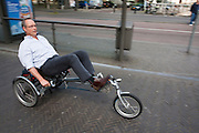 Een man rijdt op een ligfiets door Utrecht.<br />