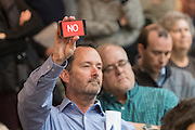 """A member of the audience holds up his phone with the word """"NO"""" during a heated discussion with U.S. Sen. Tim Scott and U.S. Rep. Mark Sanford at a town hall meeting February 18, 2017 in Mount Pleasant, South Carolina. Hundreds of concerned residents turned up for the meeting to address their opposition to President Donald Trump during a vocal meeting held by U.S. Rep. Mark Sanford and Senator Tim Scott."""