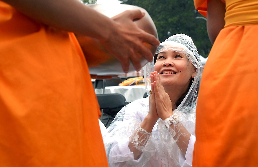 A Vietnamese woman, gives Alms to a Bhuddist monk during the annual South Asia Festival in Fairfax.