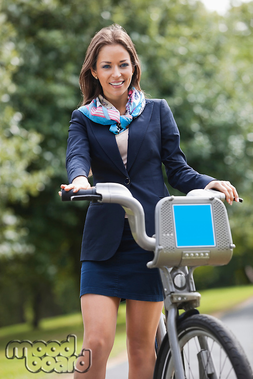 Young businesswoman with bicycle standing at park