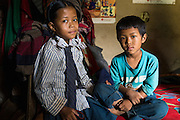 Binita (10) and her brother Sonam Tamang (7) pose for a portrait in their temporary shelter in Kavre, Bagmati, Nepal on 30 June 2015.  Their mother, Kalpana, a widow with 3 children, has been supported by SOS Children's Villages for many years now and had receive the Home-in-a-Box after the earthquake destroyed her house, almost killing her two daughters. She now lives in a temporary shelter, sharing her dwelling with farm animals, and is trying to make ends meet by weaving bamboo baskets to supplement the financial assistance provided by SOS Childrens Villages. The NGO mostly supports her children's welfare and schooling as well as provides her with essential household and schooling items like kitchen utensils and school books and uniforms. Photo by Suzanne Lee for SOS Children's Villages