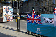 On the day that the EU in Brussels agreed in principle to extend Brexit until 31st January 2020 (aka 'Flextension') and not 31st October 2019, a tour bus drives past Brexit Party flags and banners during a Brexit protest outside parliament, on 28th October 2019, in Westminster, London, England.