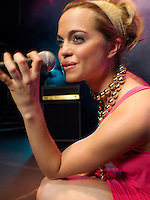 Young Woman Singing on stage in Concert close up side view