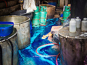 13 SEPTEMBER 2013 - BANGKOK, THAILAND: Blue dye goes down the drain after it was used to dye a batch of silk threads in workshop in a home in the Ban Krua section of Bangkok dyes silk threads. After the threads are dyed they are woven into silk. Many of the silk making families in Ban Krua are Cham Muslims from Cambodia who settled in Bangkok in the early 19th century after Rama I, the King of Siam at the time, offered them land in exchange for their services in a war against the Khmer (Cambodia) empire. The late Jim Thompson, founder of Jim Thompson Thai Silk, first made the silk weavers famous when he bought most of his silk from them.         PHOTO BY JACK KURTZ