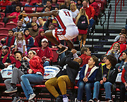 UNLV forward Cheickna Dembele (11) leaps into the stands chasing a loose ball and does his best to avoid the fans during their game at the Thomas & Mack Center on Saturday, Nov. 19, 2016.