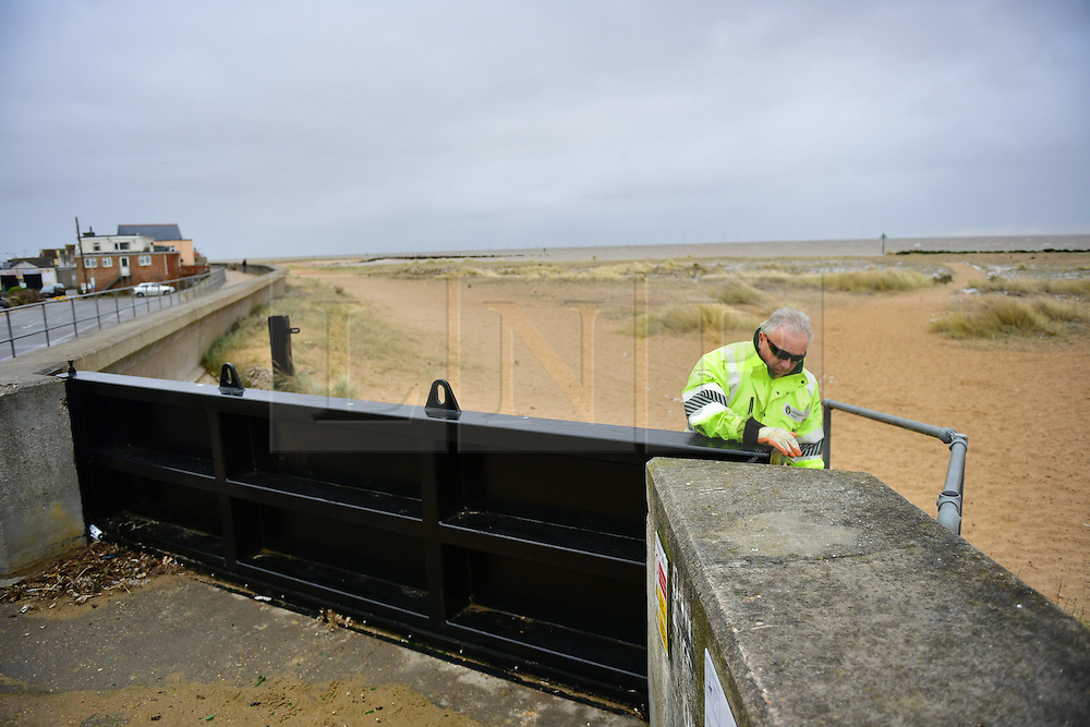 © Licensed to London News Pictures. 13/01/2017. Jaywick, UK. A member of the environment agency checks a flood defence barrier on the seafront at Jaywick before Homes are evacuated due to the threat of flooding in low-lying areas . Photo credit: Ben Cawthra/LNP