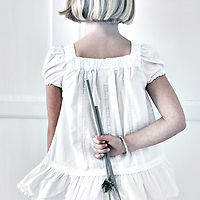 Young girl with blonde hair facing away from camera holding flowers behind her back