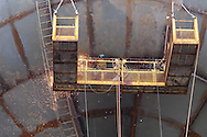 Welders work from platform suspended from half-built water tower to connect and close gaps in huge steel plates; Kirkwood, Missouri.